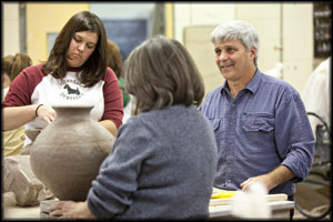 Joe Molinaro works with students in Ceramics